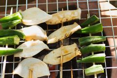 Mushrooms and raw okra Grilled in a saucepan, seasoned with seasoning. Use as a snack between meals.  Royalty Free Stock Image