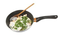 Mushrooms with sauce in a wok. Baby mushrooms with a cream sauce and herbs in a wok isolated against white royalty free stock image