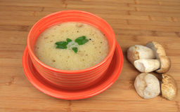 Mushrooms soup. In bowl on wooden table with fresh mushrooms Stock Photos