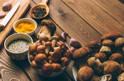 Mushrooms and spices on a kitchen wooden table, selective focus Royalty Free Stock Images