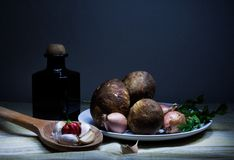 Mushrooms. Still life with mushrooms,  black bottle with olive oil, onion, garlic and pepper Royalty Free Stock Photos