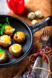 Mushrooms stuffed with quail egg on black pan Stock Photo