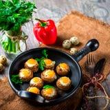 Mushrooms stuffed with quail egg on black pan Royalty Free Stock Image