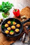 Mushrooms stuffed with quail egg on black pan Stock Photography