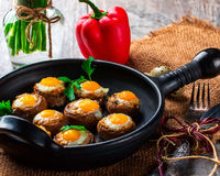 Mushrooms stuffed with quail egg on black pan Stock Photos