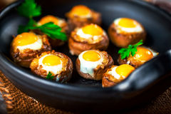 Mushrooms stuffed with quail egg on black pan Royalty Free Stock Photography