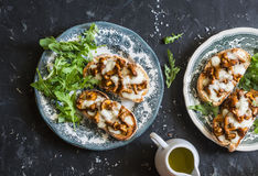 Mushrooms tartine. Baked sandwiches with mushrooms chanterelles and mozzarella on a dark background. Top view stock photo