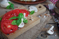 Mushrooms, tomatoes and basil. On rustic wooden table Royalty Free Stock Image