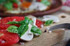 Mushrooms, tomatoes and basil. On rustic wooden table Stock Image