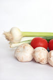 Mushrooms and tomatoes. Field mushrooms, tomatoes, stalks of onions napiform and garlic on a vertical photo Stock Image