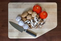 Mushrooms Tomatoes Garlic Cloves Kitchen Knife on Cutting Board. Mushrooms tomatoes garlic cloves vegetable with kitchen knife on wood cutting board Stock Photos