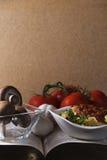 Mushrooms Tomatoes and Garlic on Cork Background Stock Photo