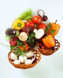 Mushrooms and a variety of fresh vegetables in a wicker basket.isolated on a white. Background.photo with copy space Stock Photos
