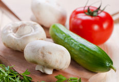 Mushrooms and vegetables on board. Mushrooms and vegetables on cutting board Stock Image