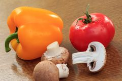 Mushrooms, yellow pepper and red tomato on the kitchen table. Mushrooms, yellow pepper and red tomato on the wooden kitchen table. Fresh vegetables royalty free stock photo