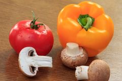 Mushrooms, yellow pepper and red tomato on the kitchen table. Mushrooms, yellow pepper and red tomato on the wooden kitchen table. Fresh vegetables stock photo