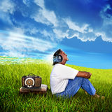 Music. A man sits with his back toward a vintage radio with headphones on his head.  Music waves with notes stream from the headphones.  Grass field with cloudy