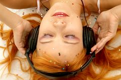 Music. Pretty redhead listening music Royalty Free Stock Image