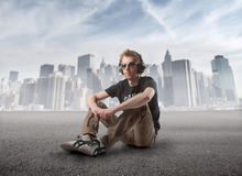 Music. Young man sitting on a street and listening to music with cityscape on the background Royalty Free Stock Photography