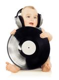 Music. Portrait of cheerful child in headphones with music disk stock image