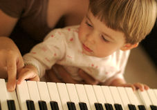 Music. A child playing a keyboard