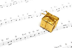 Music. A small golden present on top of some sheetmusic Stock Photos