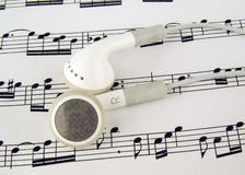 Music. Headphones on some sheet music ready for listening Stock Photo
