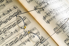 Music. A pair of rimmed glasses on a music sheet Stock Image