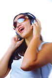 In music. Blurrier portrait   of young  female listening music via earphones. Focused on face Royalty Free Stock Photos