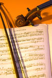 Music. Violin's scroll, pegbox and bow next to a sheet music stock images