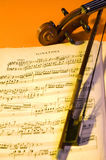Music. Violin's scroll, pegbox and bow next to a sheet music Stock Image