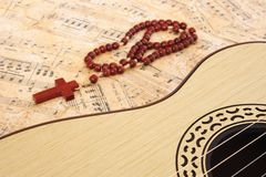 Music. Guitar and  crucifix on a music sheet Royalty Free Stock Images
