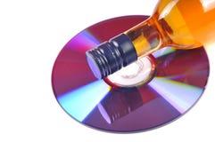 Music addiction. Music cd with wine bottle isolated on white background Stock Image