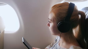Music in the air. Woman in headphones with your smartphone to fly in an airplane. Young attractive woman is flying in an airplane. It uses a smartphone listening stock video footage