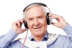 Music for all ages. Portrait of senior man in headphones listening to music and smiling while standing against white background royalty free stock photos