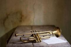 Music. An ancient old jazz trumpet in a old house with a musical keys Stock Image