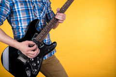 Free Music And Art. The Guitarist Plays The Electric Guitar On A Yellow Isolated Background. Playing Guitar. Horizontal Frame Royalty Free Stock Images - 92618709