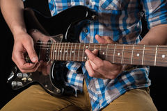 Music and art. Electric guitar in the hands of a guitarist, on a black isolated background. Playing guitar. Horizontal frame Stock Photos