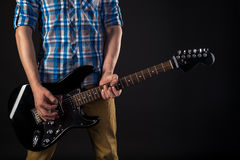 Music and art. The guitarist holds an electric guitar in his hands, on a black isolated background. Playing guitar. Horizontal fra Stock Images