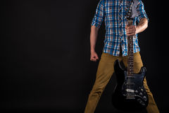 Music and art. The guitarist holds an electric guitar in his left hand, on a black isolated background. Playing guitar. Horizontal Stock Images