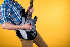 Music and art. The guitarist plays the electric guitar on a yellow isolated background. Playing guitar. Horizontal frame Stock Photo