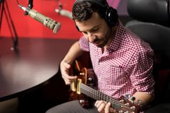 Music artist playing guitar in radio show. Handsome young male singer wearing headphones singing song and playing guitar in radio station Royalty Free Stock Photography