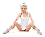 Music babe. Sexy woman in white shirt and sunglasses sitting on a floor and listening for the music using headphones Stock Photography
