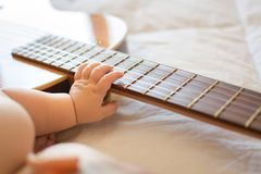 Baby arm on guitar royalty free stock photo