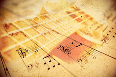 Music background. Abstract music note sheets background with ukulele overlay Royalty Free Stock Photo