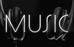 Music background. Blurred headphones on the background and the written `Music` on the front. Shining music word on a dark background Stock Photo