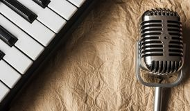 Music background with piano and retro microphone. On grunge paper texture Stock Image