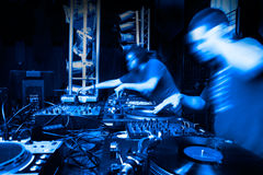 Music backgrounds with disc-jockey. Image of two disc-jockey with several mixers royalty free stock image