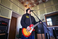 Music band Brutto performing in a recording studio. A rock band Brutto is working in studio. vocalist Denys Mel`nik Left is singing with a guitar in his hands Stock Photography