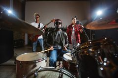 Music band. Modern rock band of three musicians playing drums, guitar and performing songs royalty free stock photos